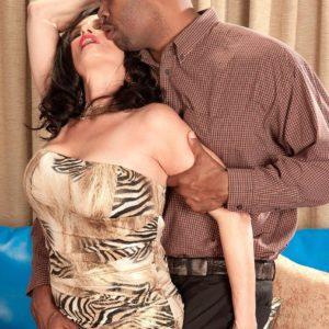 Mature brown-haired adult flick star Rita Daniels freeing humungous boobs before multiracial sex