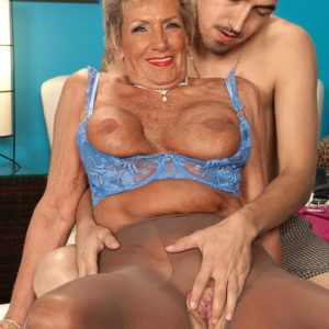 Pantyhose wearing 70 plus MILF Sandra Ann uncovering giant titties before sex with junior dude