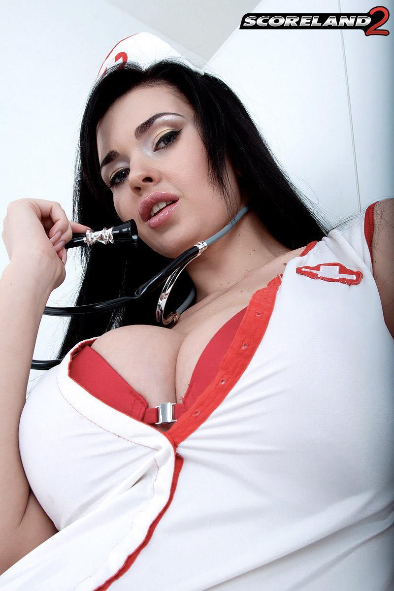 Dark-haired nurse Sha Rizel removes her uniform to pose in her melon-holder and underwear