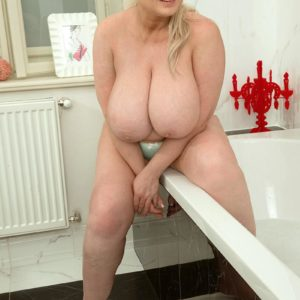 Blond BIG SEXY LADY Samantha Sanders lets out her monster-sized melons as she readies for a tub