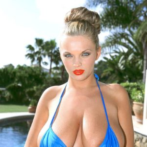 Blonde solo female Ines Cudna sets her enormous all natural boobs free from swimsuit top by the pool