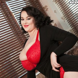 Chubber dark haired solo model Lila Payne poses in a crimson boulder-holder and tan pantyhose on futon