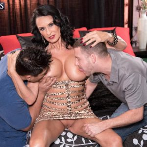 Experienced black-haired X-rated star Rita Daniels showcasing no panty upskirt during titty slurping