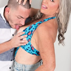 Sumptuous 60 plus MILF Silva Foxx seduces a junior boy by displaying her funbags in a denim micro-skirt