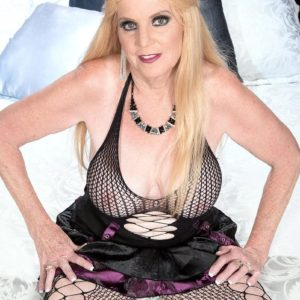 Blond grandmother Charlie frees her humungous juggs in over the knee boots and mesh body-stocking