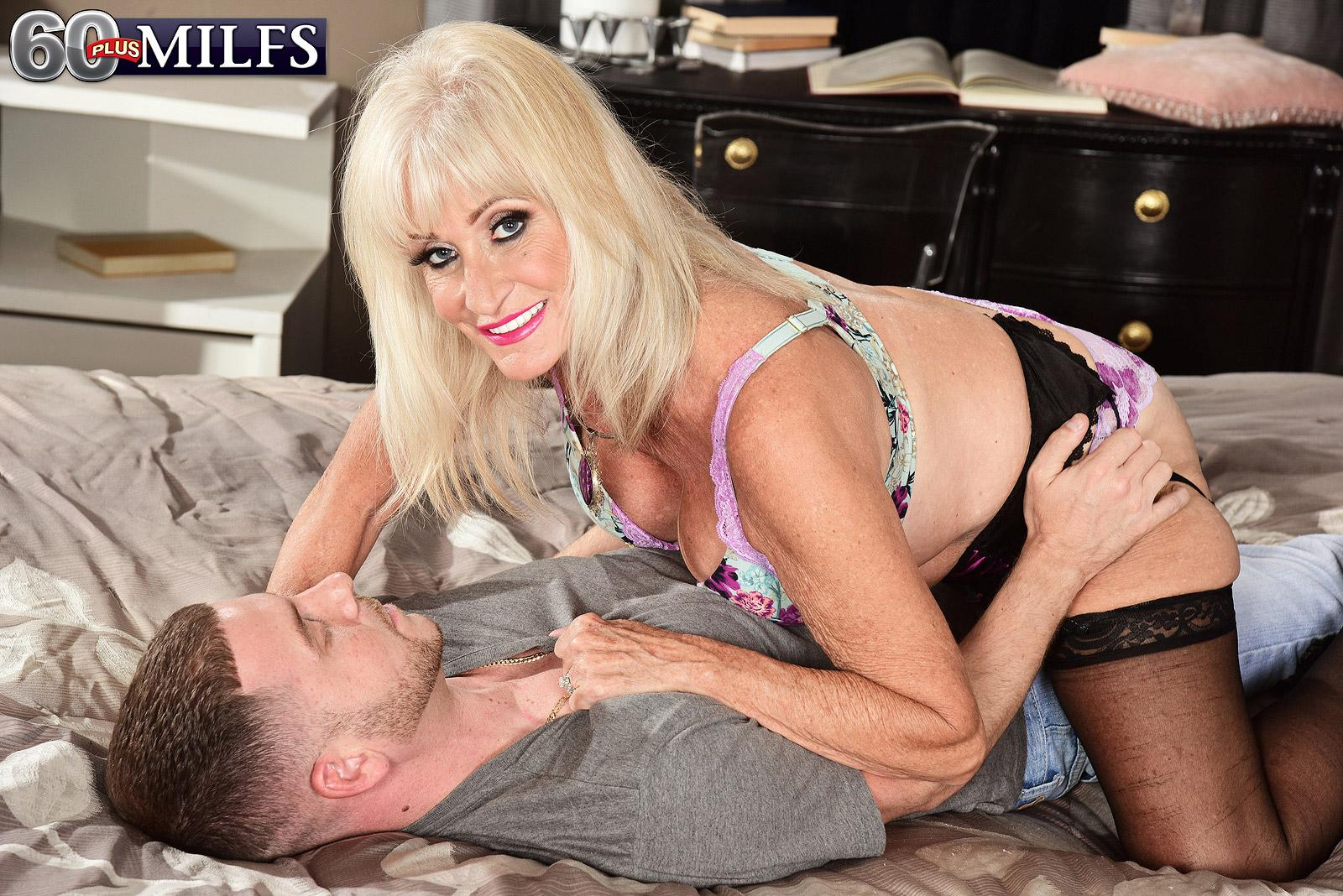 Blonde grandma Leah L'Amour gives her boy toy a hand job in lingerie and hose