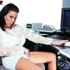 Brunette MILF Linsey Dawn McKenzie unveils her monster-sized titties at her office desk