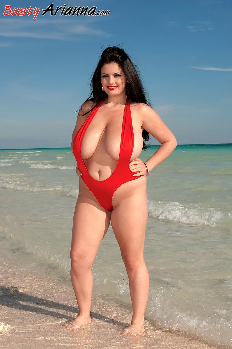 Brown-haired big sexy woman Arianna Sinn bares her huge boobies from bathing suit at the beach