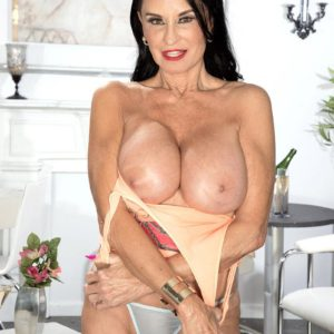 Top aged adult film star Rita Daniels unsheathes her immense breasts and displays her underwear as well