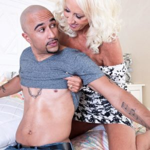 Enticing 60 plus MILF Madison Milstar tempts a younger black man in a taut fitting dress
