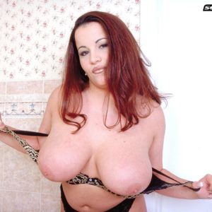 Ginger-haired MILF Annie Swanson wets her giant juggs in the bath during solo act
