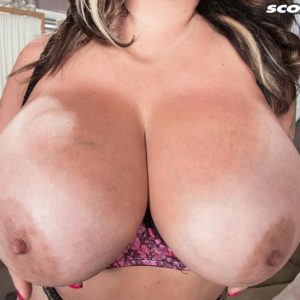 Tatted black-haired MILF Amaya May frees her big tits from her boulder-holder in a mini-skirt