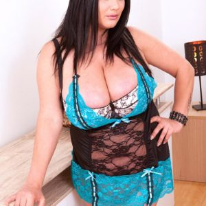 Brunette BIG HOT WOMAN Nila Mason models fully clothed in killer lingerie and nylons in bedroom