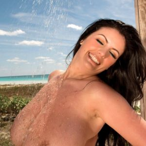 Dark-haired MILF Arianna Sinn flaunts her big juggs in the outdoors with the ocean in view