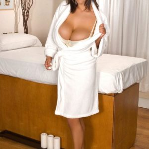 Solo girl Eva Notty releases her huge boobs from her bra while readying for a massage