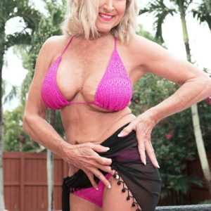 Hot 60 plus woman Katia has her big boobs fondled by younger man on patio