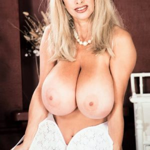 Famous pornstar Alexis Love uncups her massive boobs in white nylons and red heels