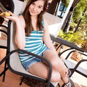 Brunette teen Kasey Warner eats a banana before exposing her flat chest outdoors
