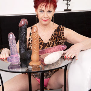 Redhead granny Caroline Hamsel munches and deepthroats her bevy of sex toys in panties