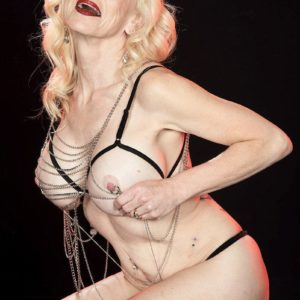 Elder ash-blonde Cammille Austin wears nip forceps while modelling transparent lingerie