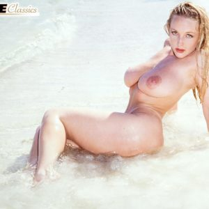 Golden-haired solo female Danni Ashe rocks her superb boobies while nude as the surf enters