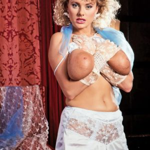 Curly yellow-haired Suzanne Brecht uncovers her monster-sized titties in lace lingerie and gloves
