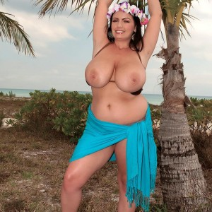 Chunky female Arianna Sinn uncups her fun bags as she gets nude by a tropical tree