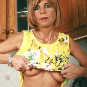 Middle older housewife peels off denim jeans and panties to model naked in kitchen