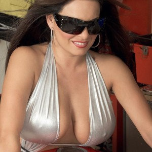 Brown-haired MILF Mia Starr revealing immense all natural titties on motorcycle in sunglasses