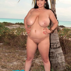 Plumper female Arianna Sinn uncups her melons as she gets naked by a tropical tree