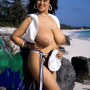 Dark-haired MILF Lisa Phillips touts her gigantic breasts and butt on a sandy beach