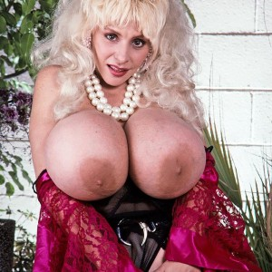 Well known pornstar Lulu Devine releases her humungous breasts in see-through tights and garters